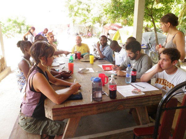 Haitian students and international volunteers sit at a picnic table chatting and writing notes while getting to know each other