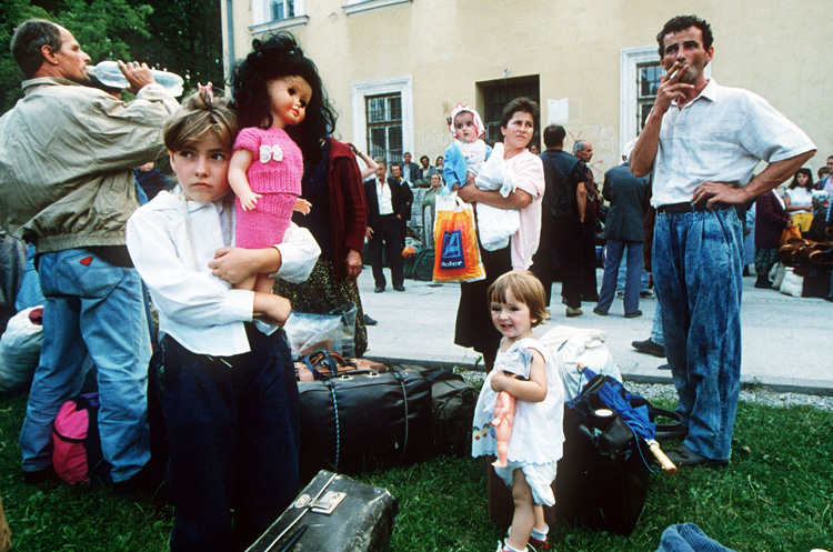 Croation adult and child refugees arrive in Travnik, central Bosnia, during the Bosnian War, 1993. They carry personal belongings in suitcases, supermarket carrier bags and duffel bags.